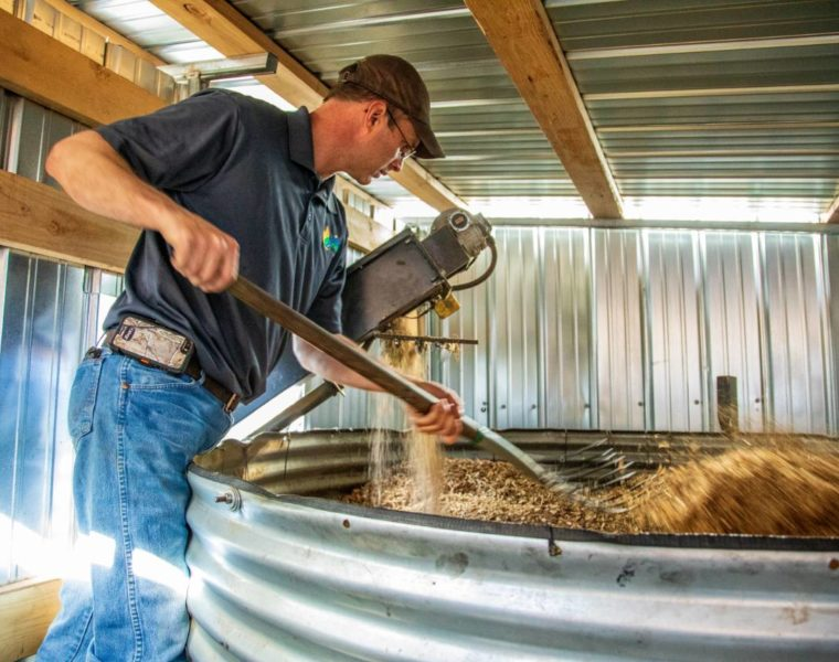 Rowdy Yeatts stirs woodchips in a hopper, in preparation for cooking them into biochar. Credit: Impact Media Lab / AAAS