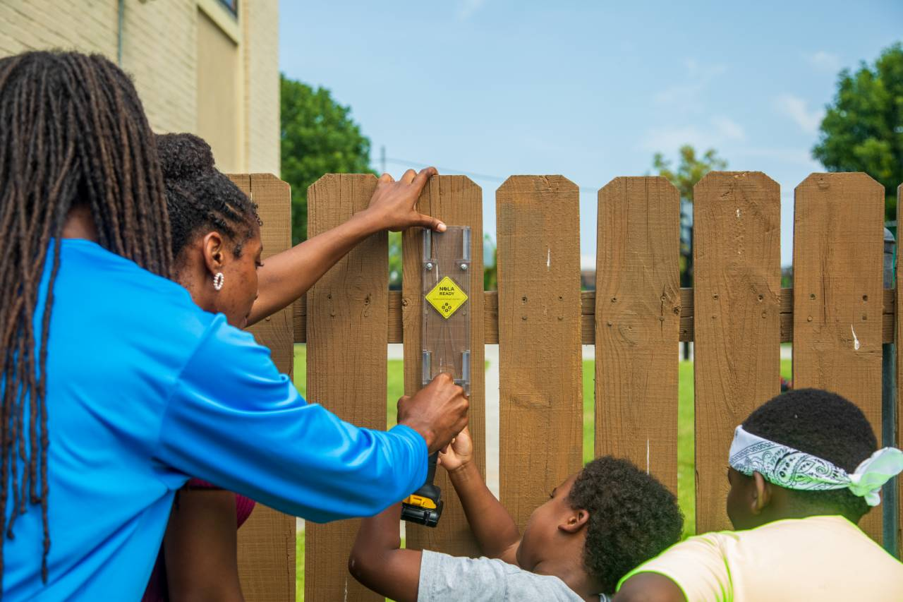 ISeeChange ambassador Yasmin Davis gets some help from students and teachers to install a rain gauge at a community center in New Orleans, Louisiana. Credit: Impact Media Lab / AAAS