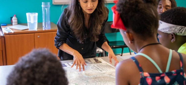 Founder of ISeeChange, Julia Kumari Drapkin, shows children a map of historic New Orleans. Drapkin highlights the parts of the city that used to be swamp. Credit: Impact Media Lab / AAAS