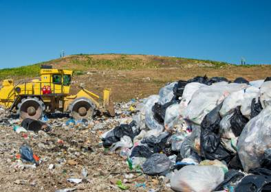 A tractor moves piles of trash at the Dane County Landfill.