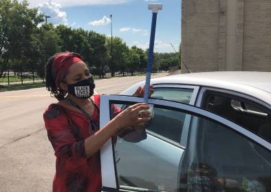 Dr. Hines, from Jackson State University, setting heat mapping equipment on a volunteer's car, August, 2020